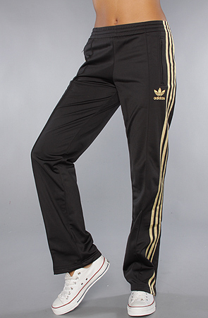 328288419a83 The Firebird Track Pant In Black Gold. Adidas Womens Black Pants Gold  Stripe Angle Stand Pose